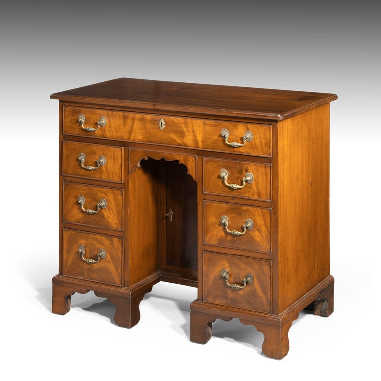 A George III period mahogany kneeholes desk of small proportions. With good original bracket feet and finely cast swan neck handles. With a central cupboard.