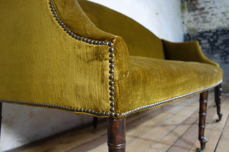 An elegant George III settee, raised on eight faux bamboo mahogany legs terminating on pad feet - sat on brass castors. Upholstered in a period honey yellow velvet, with some signs of age and wear throughout. Of good proportions demonstrating a