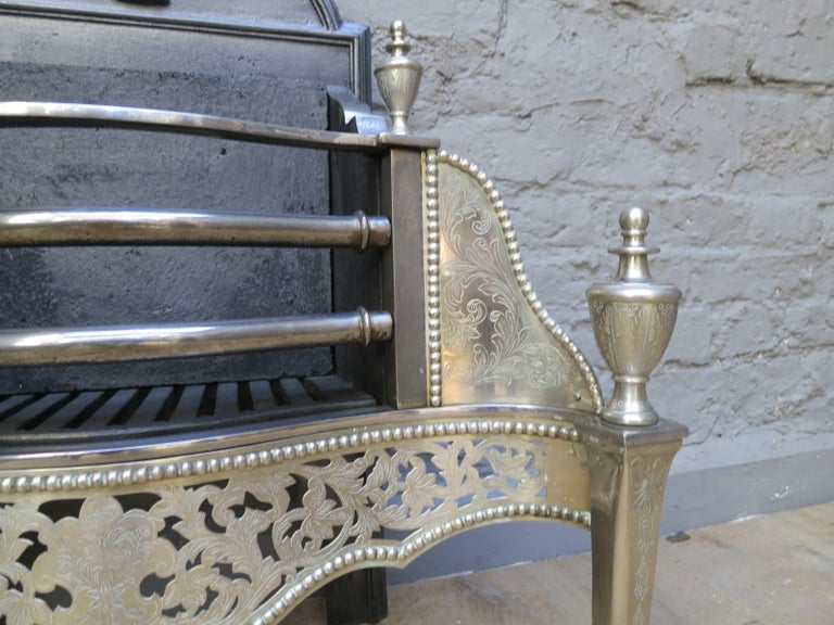 A good quality 20th century copy of a Georgian style grate. The tapering front supports engraved as are the surmounting finials. The bowed front bars flanked by engraved wings, with foliage pierced and beaded fret work beneath all in lacquered brass