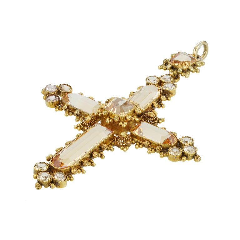 A Georgian topaz cross pendant, to the centre an octagonal-cut topaz, each arm set with a window-shape faceted topaz terminating to three small round faceted topazes, the cross suspended by an octagonal-shape topaz and gold pendant loop, the topazes