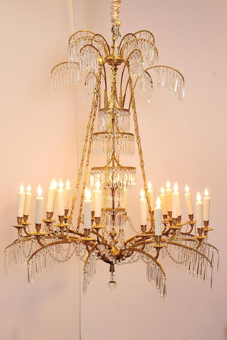 A German neoclassic ormolu and cut-glass twenty-four light chandelier, circa 1795, probably Berlin and attributable to Werner & Mieth, founded 1792, one of the great artistic foundries of the age of European Neoclassicism.   drilled for electricity,