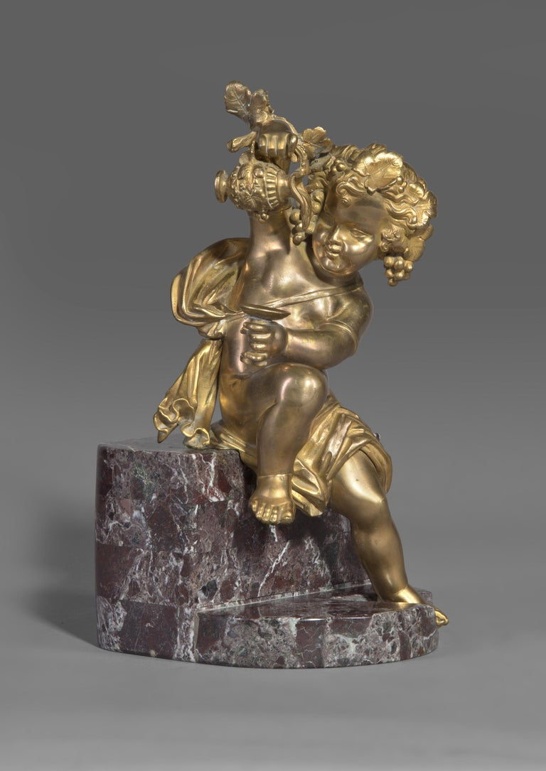 A gilt bronze bacchanalian putto figure, seated on a rouge marble plinth.  French, circa 1870.   The figure possibly originally mounted on a piece of furniture or forming part of a larger group.