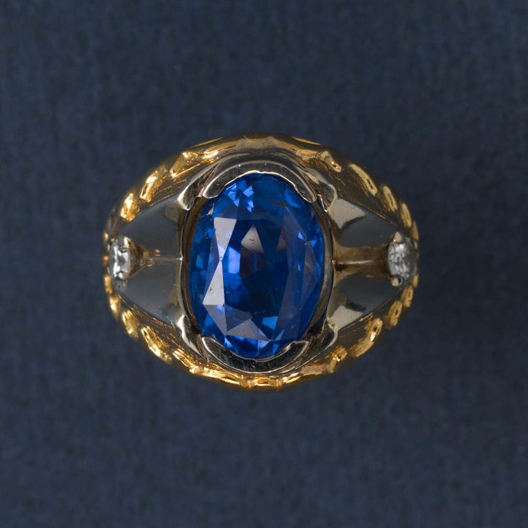 A 22 carat gold ring set with an oval facetted natural Sri Lanka sapphire (app. 11 carat), open set with on each side  a white gold angular form and a brilliant cut diamond (each app. o.25 carat), the shank is decorated with hammered and round