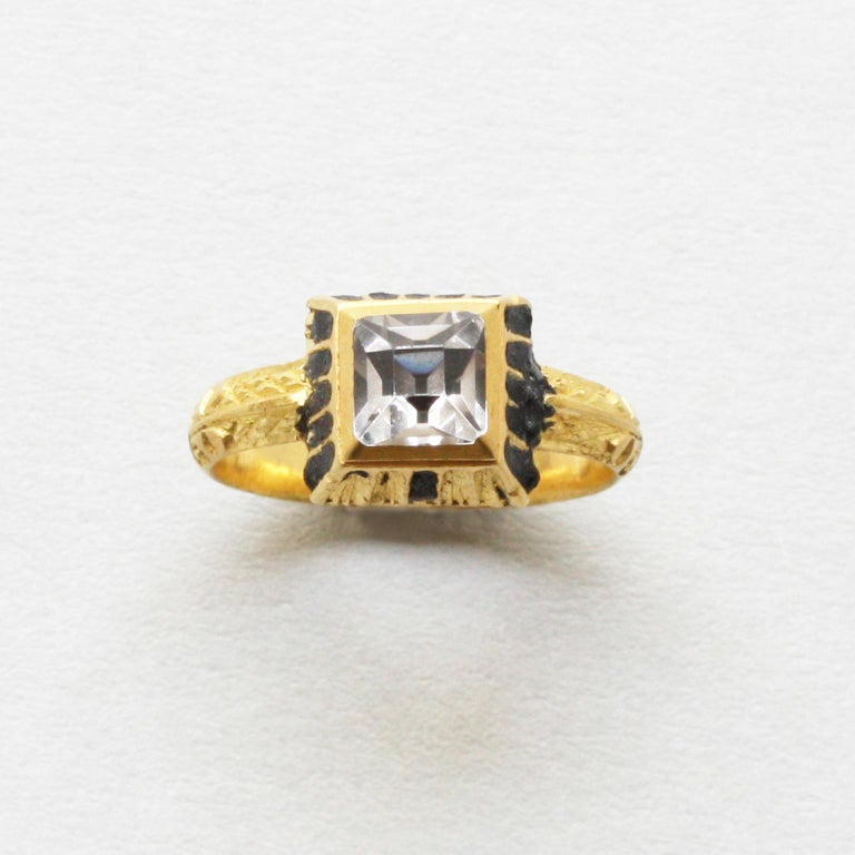 A gold ring set with a table cut rock crystal in a box setting which sides are decorated with black enamel and scrolls on the shank, marked with a star, Netherlands, circa 1600.  PAN registration number: 00078640.  ring size: 16.25 mm / 5 ¾