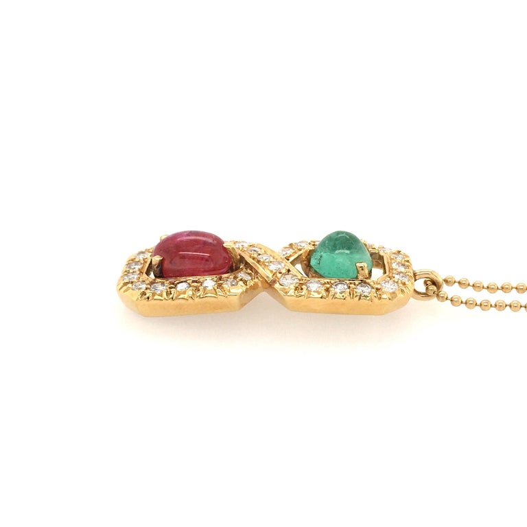 An 18 karat yellow gold, ruby, emerald and diamond pendant, with 14 karat yellow gold bead chain. Designed as a circular cut diamond set figure 8 pendant, set with an oval cabochon ruby, weighing approximately 2.40 carats and a circular sugarloaf
