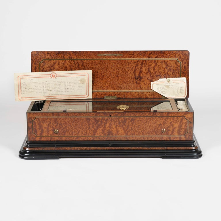 A splendid music box, numbered 20482 By B.A. Bremond of Geneva  The rectangular box, with a hinged lid, a drawer for the spare cylinders to the front, is constructed in amboyna, with boxwood stringing, and ebonised accents; there are four