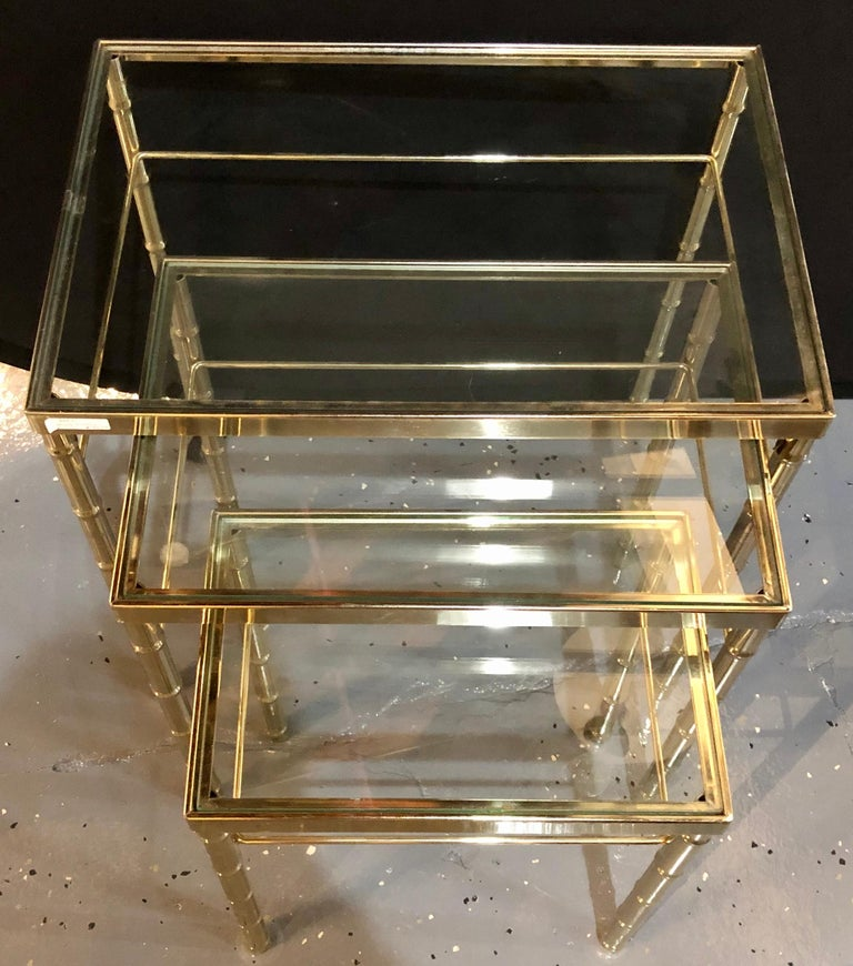 A group of three faux bamboo brass nesting tables with glass tops. These tables represent Asian and Postmodern design.