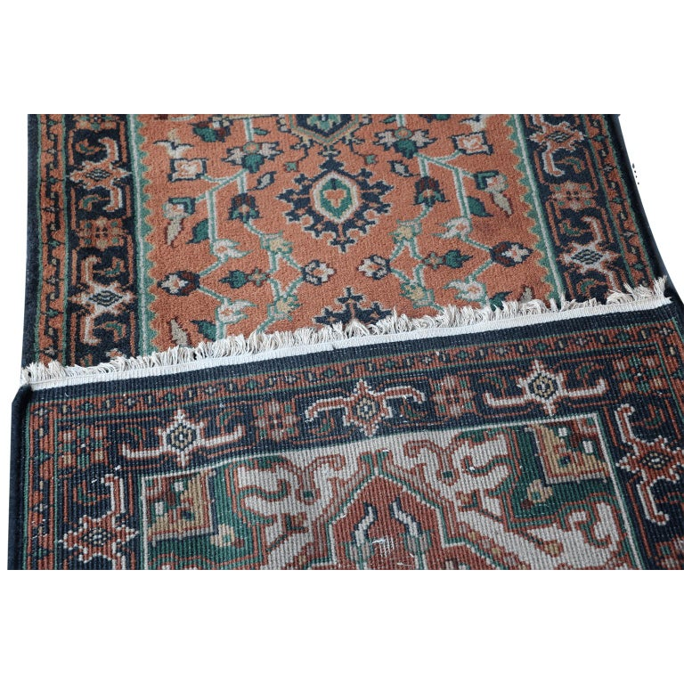 A very fine hand knotted Indo Heriz runner, North India, wool on cotton foundation  The terracotta field with two blue stepped medallions, supported by angular flowering vines, within a blue turtle palmette and angular vine border.   Extra