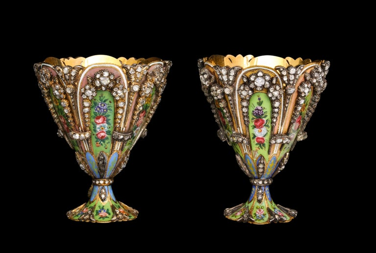 A Highly Important Museum Quality Pair of Diamond and Enamel Zarfs.  Each Zarf with  a scalloped rim and spreading foot, the sides set with colorful green and pink enamel plaques depicting flower heads and foliage. The stem and the base is a similar