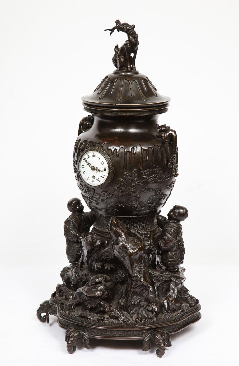 A Japanese patinated bronze figural clock vase, Meiji period, in the Japonisme taste.  Depicting two young Japanese boys holding an urn, surrounded by hills, mountains and nature, on elephant head feet. Very interesting and unusual