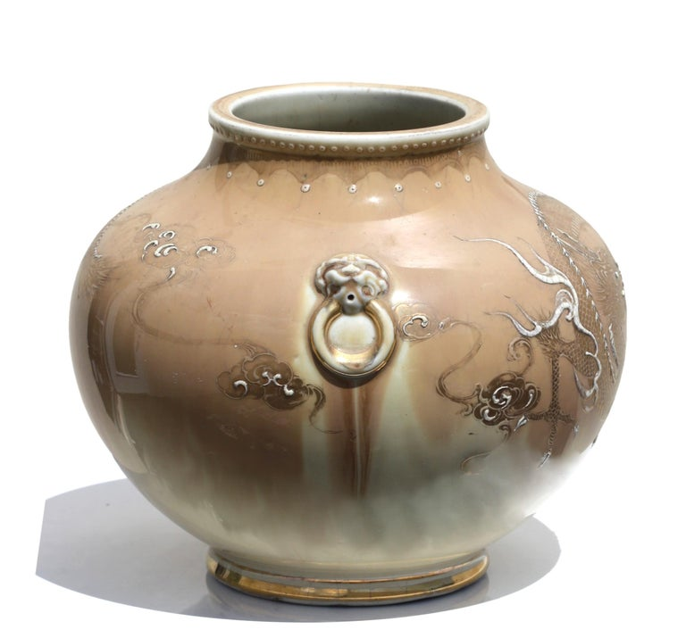 A Japanese Porcelain globular jar with dragon design on a light brown ground, early 20th century, 10 by 8 in. (25.4 x 20.32 cm.).