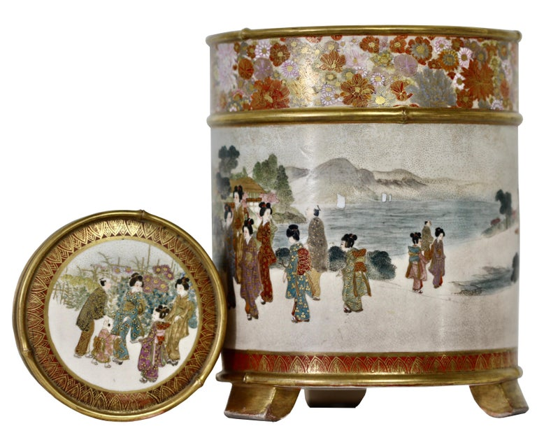 A Japanese Satsuma cylindrical koro and cover, signed Gyokuzan, Meiji period (1868-1912) Raised on three supports, painted and gilt with a continuous scene of ladies and children parading at leisure before a river scene, below a band of a