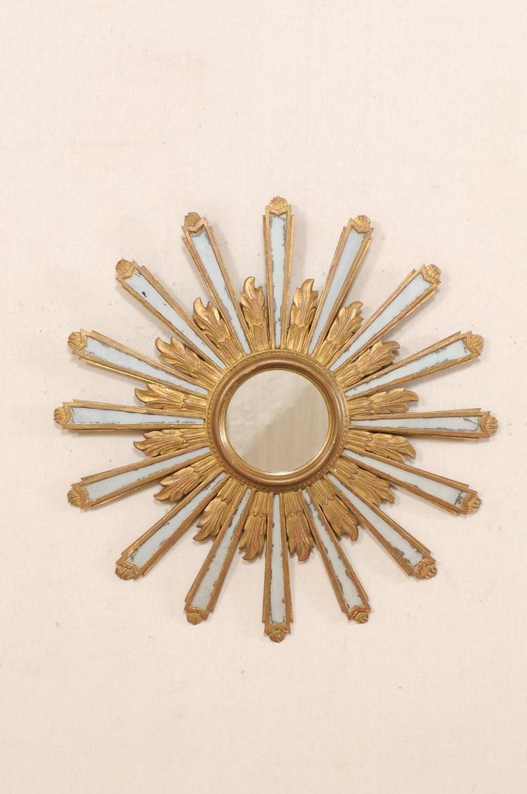 A Spanish sunburst mirror from the early 20th century. This antique mirror from Spain, just shy of 3 feet in diameter, features a circular-shaped frame with central mirror, and gilded sun-rays emerging like a halo radiating out in undulating