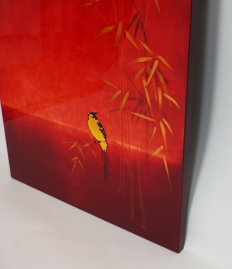 A red lacquered wall panel with a graduation of red and a yellow line reminding a sunset behind a scene of yellow bird on a bamboo stem. Signed André Dambrun (other name used by Bernard Dunand).
