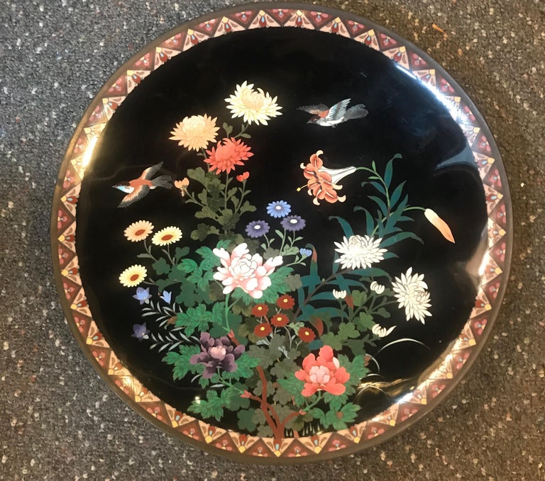 Lovely large Japanese cloisonné enamel charger Meiji Period (1868-1912). Measure: Large 14 inch.  Intricate enamel over brass cloisonné portraying a colorful floral and foliage motif with flying birds enclosed in a geometrical patterned border.
