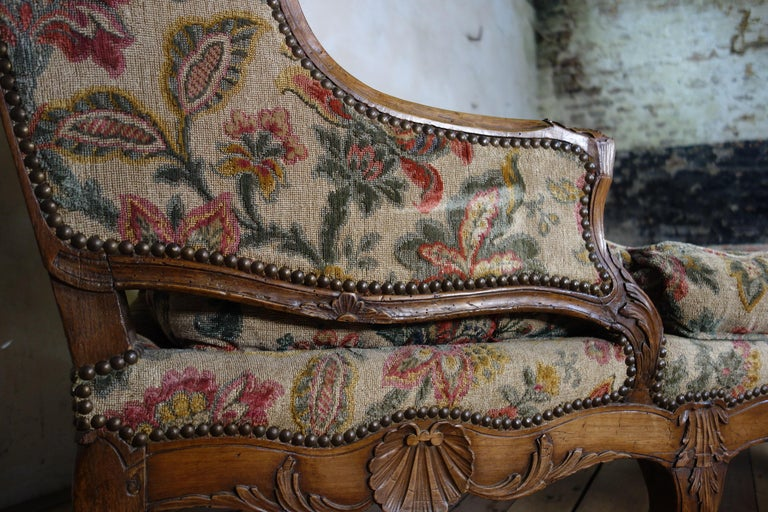 A large scale 18th century French chaise longue, raised on carved cabriole legs demonstrating scallop carvings to the serpentine seat rail. Upholstered in an extraordinary fabric, displaying rich tones throughout. 