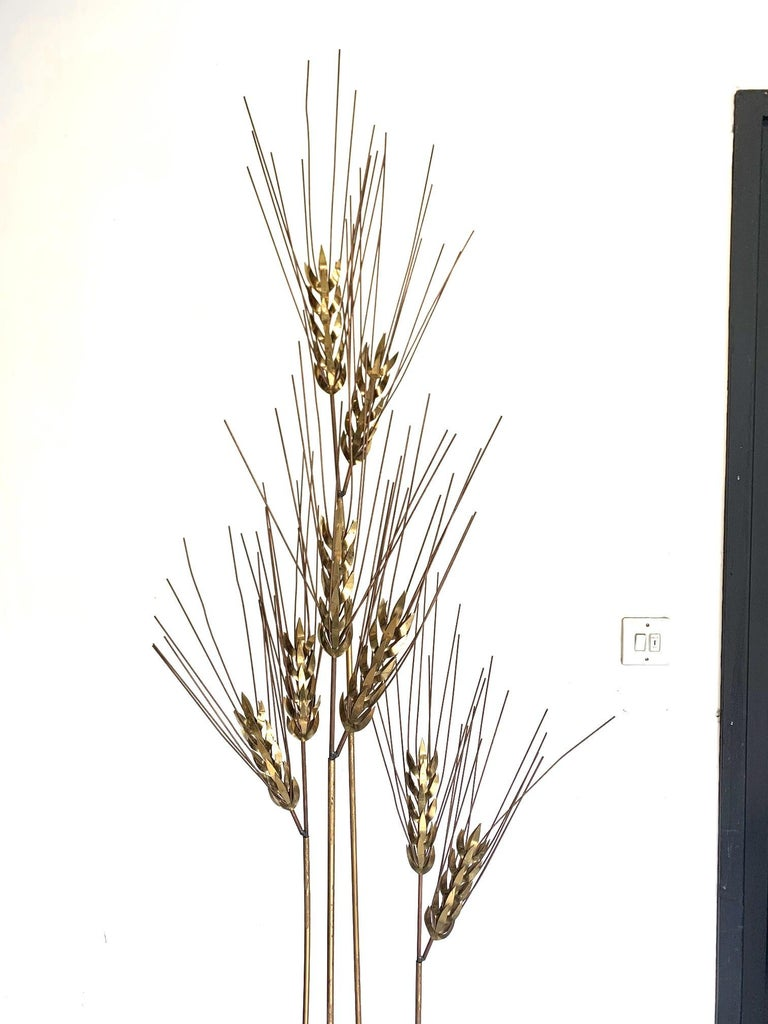 A large 1970s Curtis Jere floor standing brass and metal wheat sheaf sculpture, with four gilt metal upright from a circular twisted base, each with a large polished brass cluster of wheat ears.