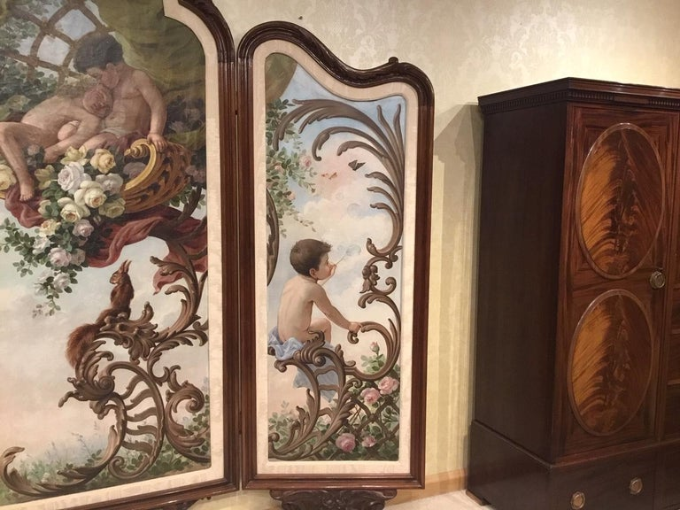 A large 19th century French walnut three fold screen in the Rococo style. The canvas panels are painted with putti amongst flowers and rocaille scrolls with two dogs looking on, French, circa 1880-1900