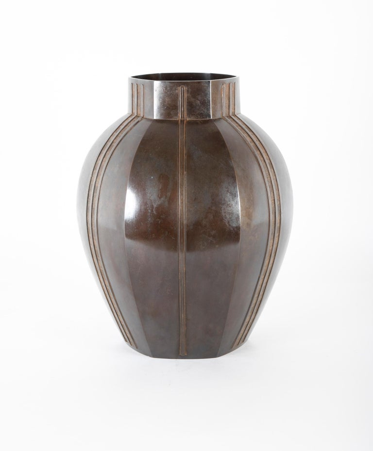 Of ovoid shape with a short neck, each panel of the body decorated with a single vertical band alternating with a double band filled with spirals and lines in relief. Original wooden box, the lid with an inscription reading Seidô ruimon rokugata