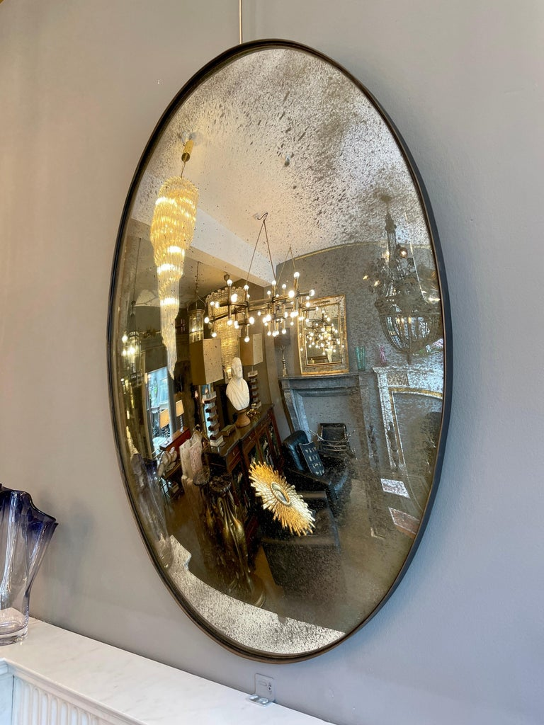 An oval shaped distressed convex mirror with bronze finish banded frame.