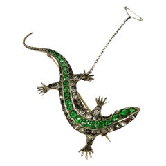 A large emerald and clear paste 'lizard' brooch, c 1900.