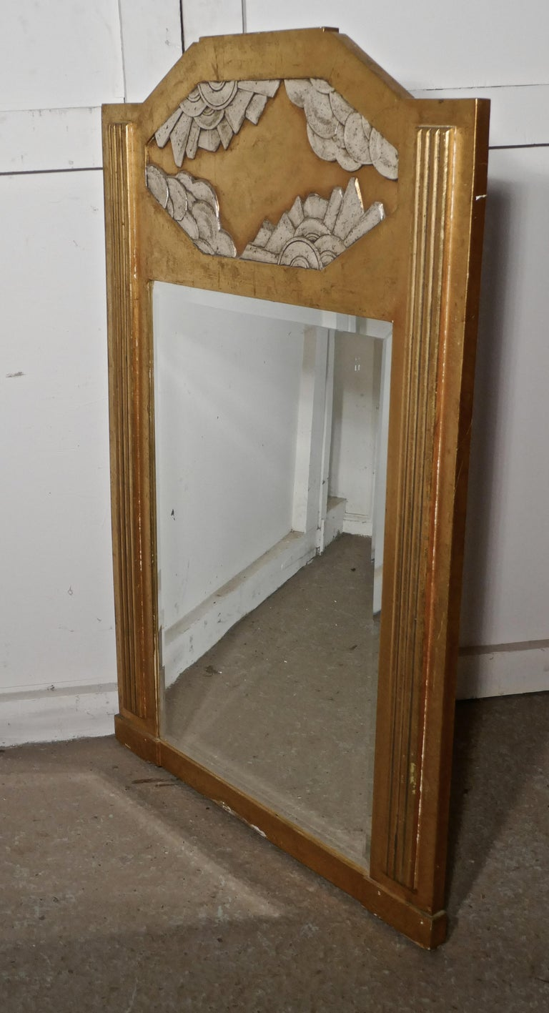 A large French Odeon style Art Deco gilt wall mirror.   This is a classic of its time, the mirror dates back to the early 1920s, it is made in wood with Gesso gold and silver finish The wide frame has reeded decoration to the sides and a large