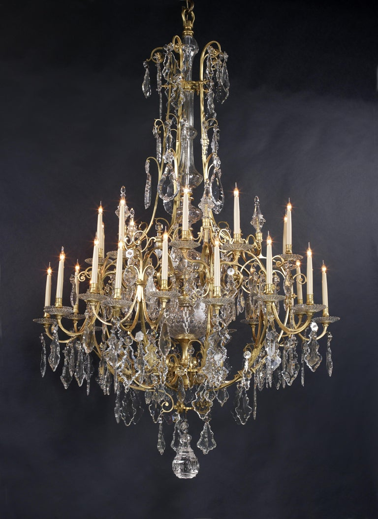 A large and important Louis XV style gilt bronze and cut-crystal thirty-light cage chandelier.  French, circa 1870.   This fine chandelier is of a grand scale at 223 cm high (88 inches).   The chandelier has a central cut-crystal baluster stem
