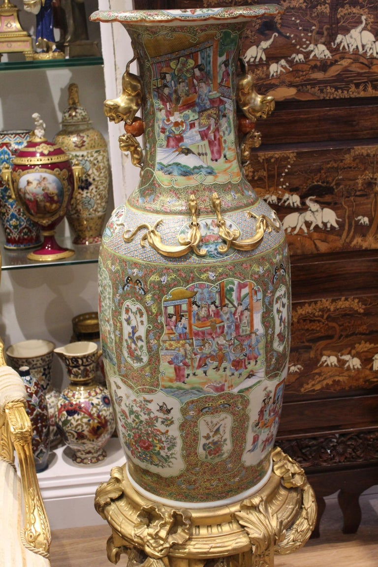 A large pair of early 19th century Chinese canton famille rose porcelain vases with twin gilt kylin handles and applied gilt relief dragons, the body decorated with vignette panels depicting court scenes together with birds and butterfly's amongst