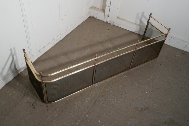 A large Victorian brass club fender 