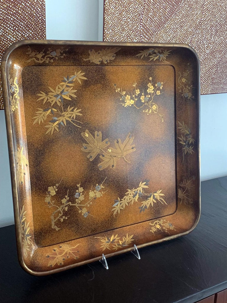 A large square lacquer presentation tray (likely for kimono) predated 1950 of the Showa period. Elaborately decorated with Maki-e that depicts the prunus blossom, bamboo and needle pine branches on a fantastic mottled Mura-Nashiji background. The
