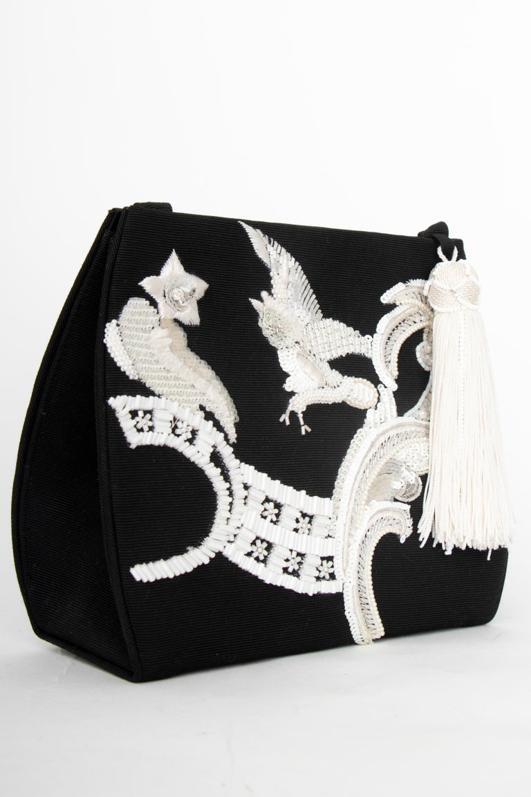 An incredible 1990s Christian Dior by John Galliano black evening bag with a thin shoulder strap and push-button closure. A bead and sequin owl and paisley motif adorn the front and a white tassel detail is placed at the top.   The bag has the