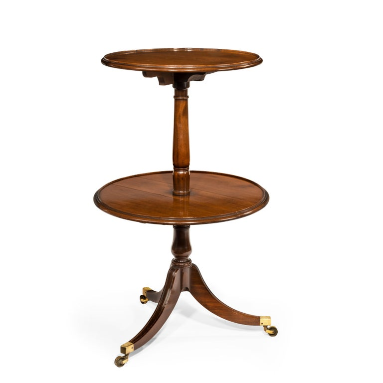 A late George III mahogany two-tier folding dumb waiter, of typical form with a central turned support raised on three square-section splayed legs with the original brass caps and castors, with two graduated circular folding shelves, each with a