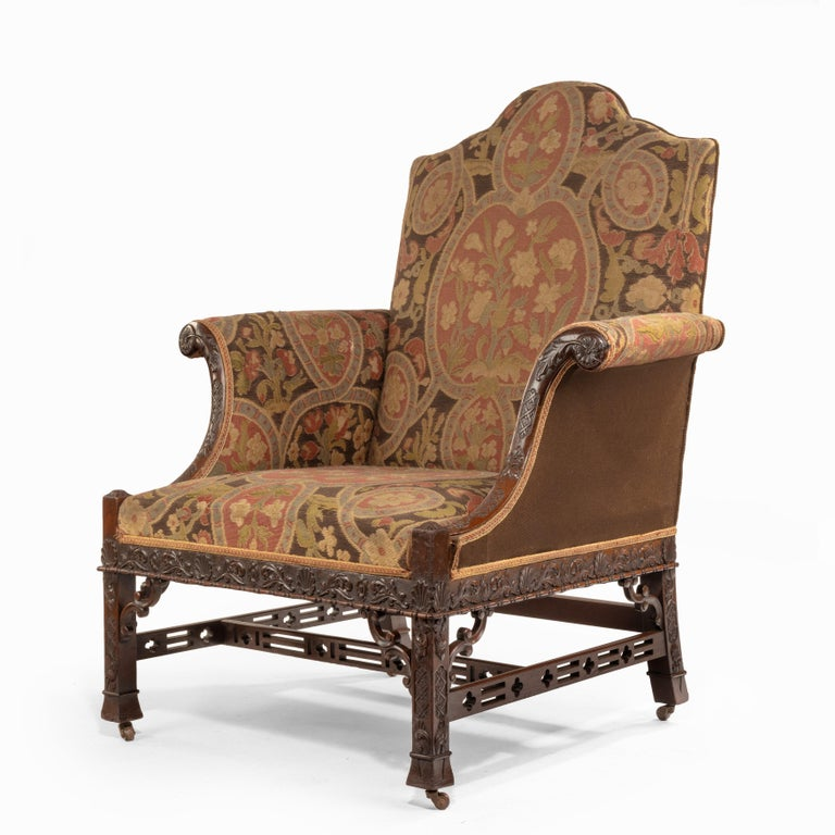 A late Victorian oversized armchair in the Chippendale manner, the scrolling mahogany arms, seat rail and legs carved with scrolling tendrils and anthemion heads, with double C-scroll spandrels and pierced stretchers, with the original needlework