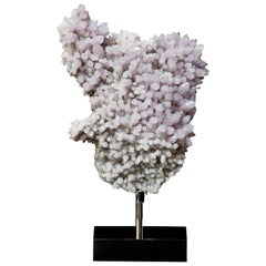 A lilac Amethyst Crystal Cluster mounted onto a mirrored steel base