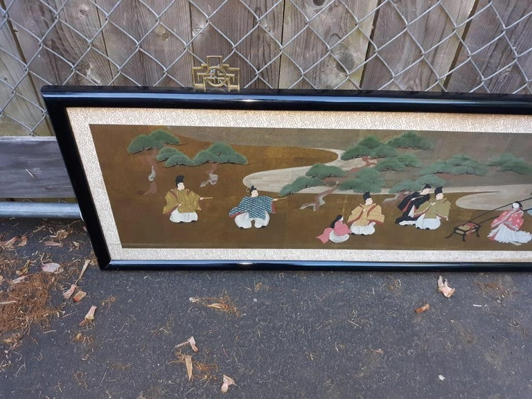 An antique horizontal Japanese Meiji period qouache watercolor painting with black lacquered frame under glass. 65.5 inches long, 17inches high. The vibrantly colored procession scene with neutral border.