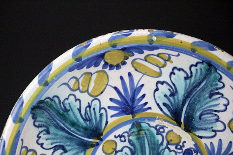 Delftware pottery charger boldly painted in the centre with a large turquoise and blue oak leaf and blue and yellow berries within a roundel surrounded by four oak leaves alternating with four stylized floral sprigs within a yellow rim border with