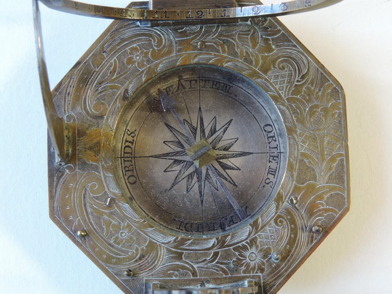 Signed L Grassl, the decorated octagonal dial with hinged hour ring, latitude arc and plumb-bob bracket, 2 3/4in (7cm) wide.