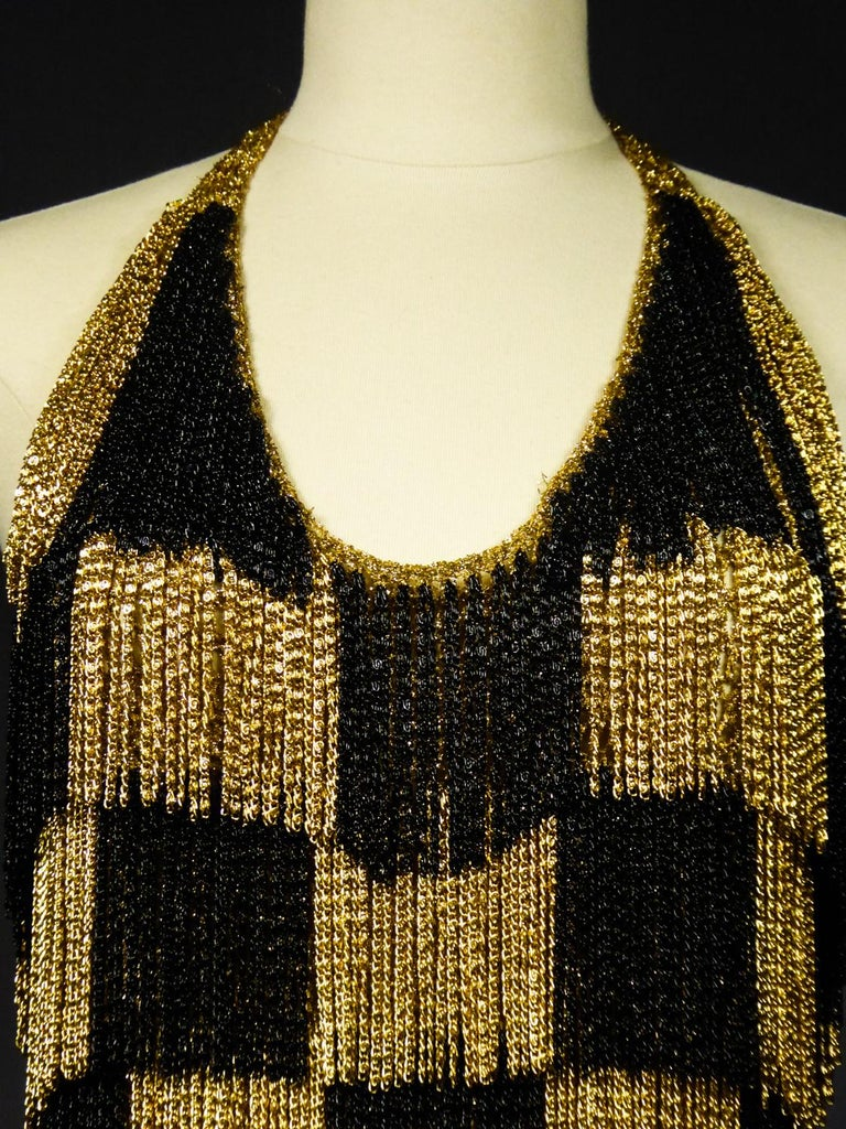 Circa 1970 France  Loris Azzaro backlesstop in gold Lurex knitwearand small gold and black chainsfrom the 1970s and the Parisian Music Hall period. Knotting of the top with Lurex ties behind the neck allowing a large plunging necklinefor the