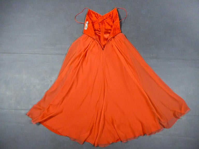 Circa 1980 France  Evening dress in orange silk crepe by Loris Azzaro Haute Couture and dating from the 1990s. Sleeveless dress with thin straps and large cleavage. High-waisted bustier with pleated work by crossed tabs highlighting the chest. Large