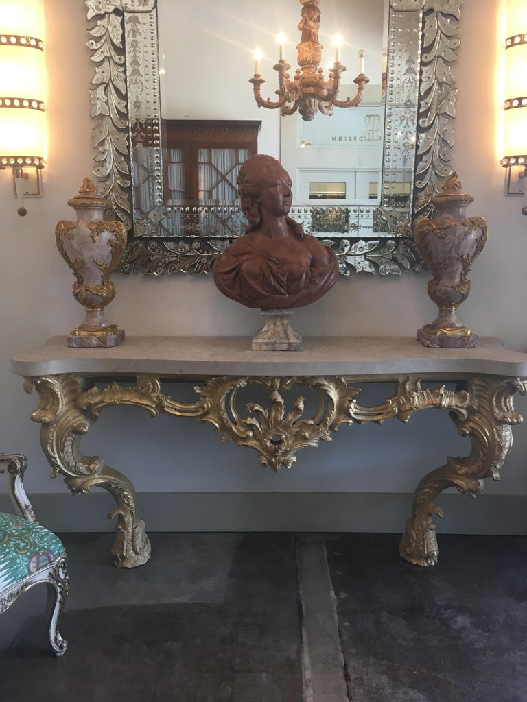 A Louis XV style carved and gilded wood console table with a thick stone top.