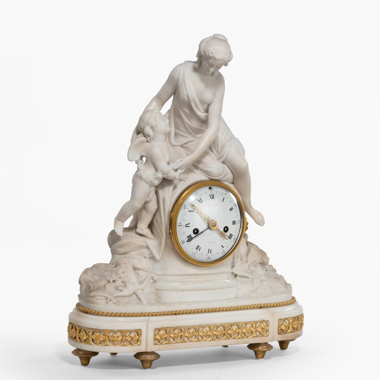 A Louis XVI period mantel (fireplace) clock by Bruel of Paris  Constructed in Carrara marble and ormolu, rising from an ormolu dressed elliptical base supported by bronze toupie feet, the figures of Psyche and Cupid rest on a rocaille ground,