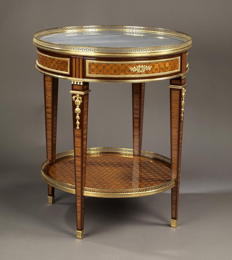 A Louis XVI style gilt bronze-mounted parquetry gueridon with a marble top.