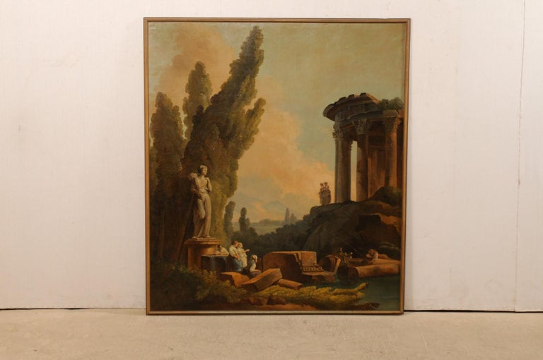 An Italian large-sized painted wall panel from the 19th century, artist unknown. This antique artisan painted and framed wall panel from Italy is a lovely capriccio depicting a classical Romanesque ruins landscape animated with maidens gathering and