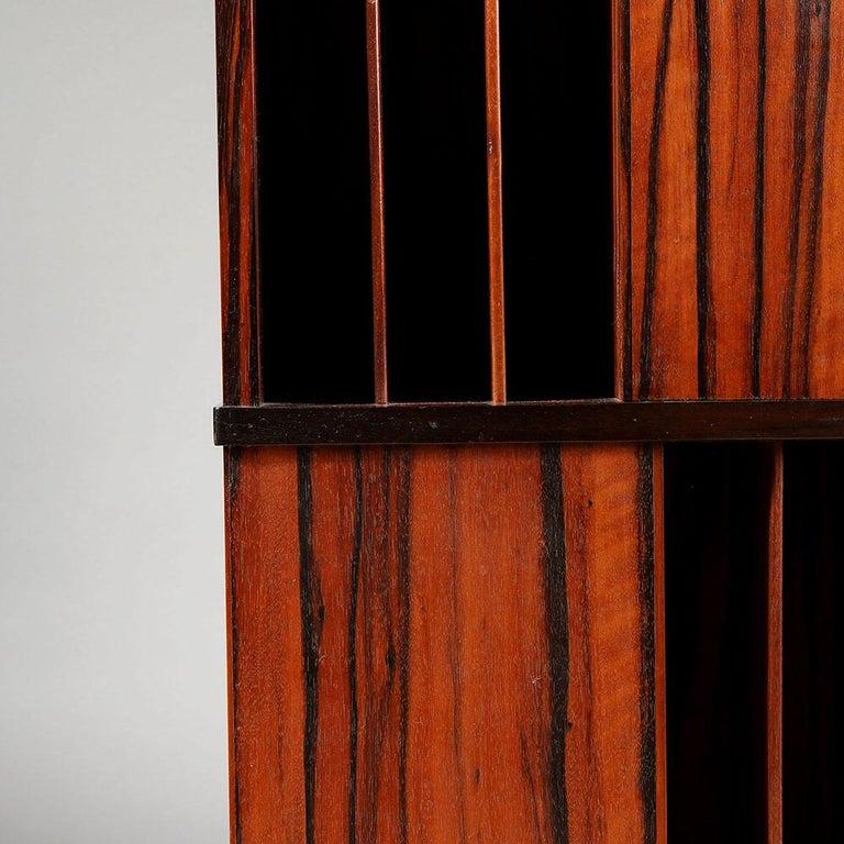 A Macassar ebony revolving bookcase, six thin shelves to each face, bun feet to the base.