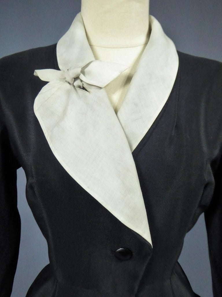Circa 1950  France Paris  Cocktail or dinner dress in black silk ottoman from the famous designer house Maguy Rouff around 1950. Dress called Redingote, open and buttoned in front, mid-length at 35 cm from the ground like the designer house Worth
