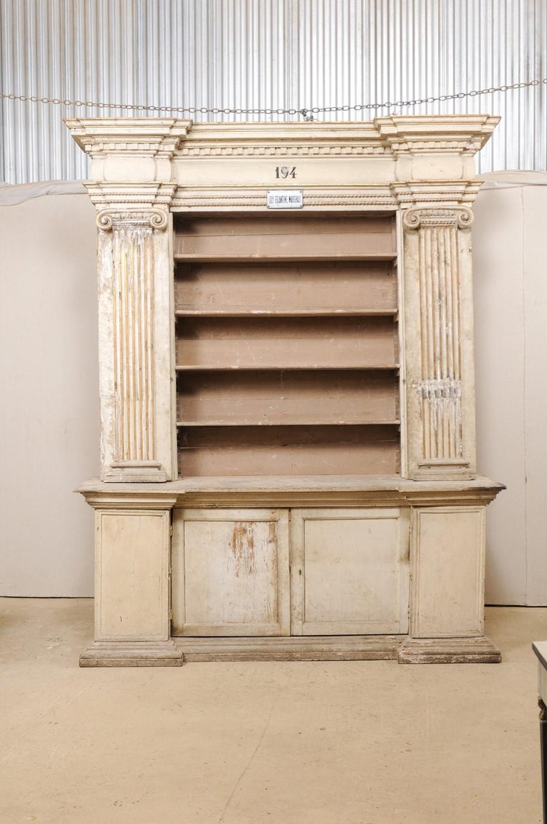 An 18th century open shelving display and closed storage cabinet from Italy, with fabulous Roman Ionic column details and retains it's original paint and gilt accents. This antique cabinet, which originally resided in an old church in Italy, is very