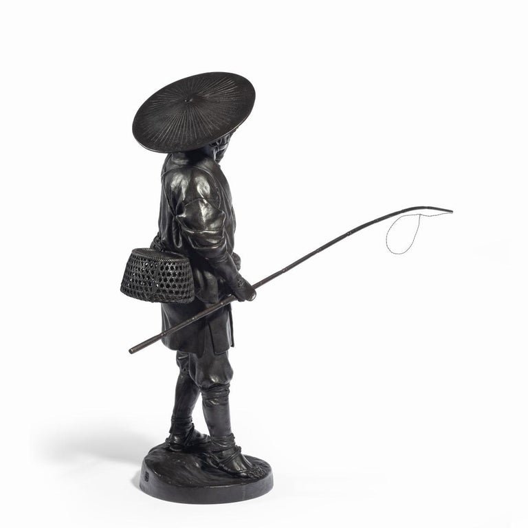 A Meiji period bronze of a cricket catcher, shown holding a whistle to his mouth with his left hand and a long rod in his right hand, wearing traditional clothing with a wide-brimmed hat and a creel slung across his back, signed in a seal. Japanese,
