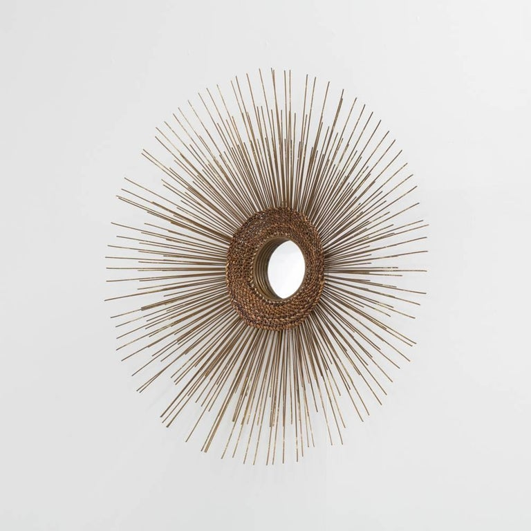 A metal starburst wall sculpture woven detail with mirror centre, 1970s.