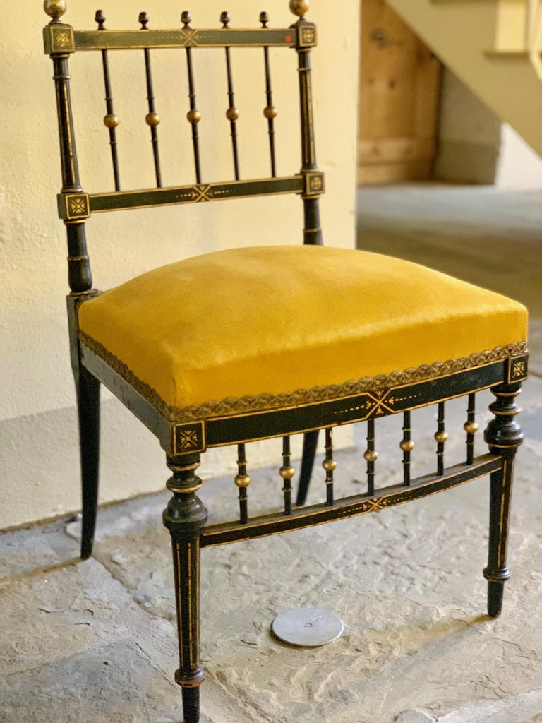 A French chair created circa 1750 in the style of ornate art furniture. The wood is ebonized fruitwood with gilded accents. The legs are tapered and turned, finished with giltwood accents. The golden cushion is finished with embroidered trim,