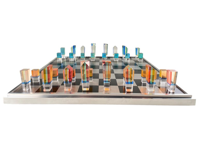 An American Mid-Century Modern acrylic and aluminum chess set by, Charles Hollis Jones with one set of pieces finished in a layered orange, yellow & red acrylic and the other pieces are yellow, blue, & green acrylic pieces together with a